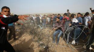 Des manifestants palestiniens sur la bande de Gaza tentent d'arracher la clotûre frontalière avec Israël, le 13 avril 2018.