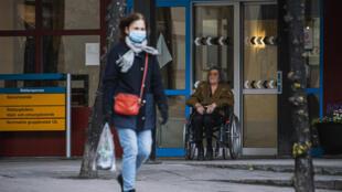 مقيمة في دار المسنين تجلس على كرسي متحرك أمام مدخل البناء في ستوكهولم في 4 أيار/مايو 2020.