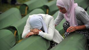 Archival picture shows a Bosnian Muslim survivor of the Srebrenica 1995 massacre cries by the coffin of a relative in the village of Potocari near the eastern-Bosnian town of Srebrenica in July 2014