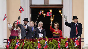 King Harald V of Norway  and his family greeted their subjects from the balcony, waving to television cameras