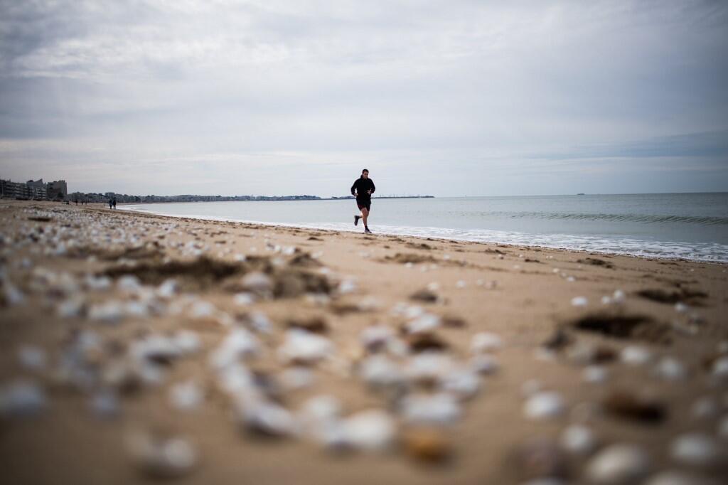 Un joggeur sur la plage de la Baule, en France, après sa réouverture, le 13 mai 2020, dans le cadre de l'assouplissement  des mesures de confinement liées au covid-19.