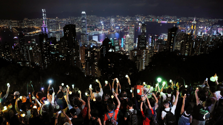 En esta foto de archivo del viernes 13 de septiembre de 2019, los manifestantes sostienen las luces del teléfono móvil mientras forman una cadena humana en Hong Kong protestando contra la ley de seguridad en junio de 2020.