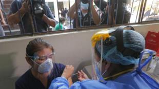 Una trabajadora de la salud peruana recibe su primera dosis de la vacuna Coronavac, durante el primer día de vacunación contra el covid-19, en Lima, el 9 de febrero de 2021
