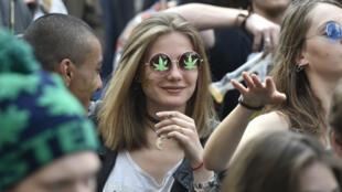 شابة تدخن خلال مهرجان سنوي تحتضنه باريس يدعو لتشريع تعاطي القنب 29 نيسان/أبريل 2017.