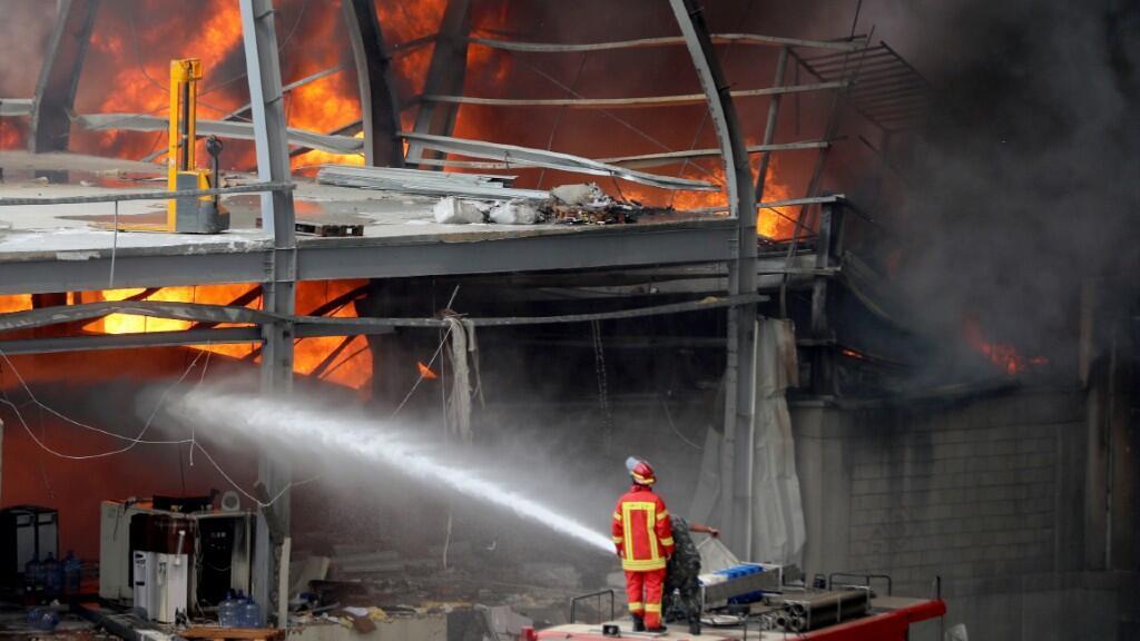 Un bombero aparece intentando sofocar las llamas del hangar con agua en Beirut, Líbano, el 10 de septiembre de 2020.