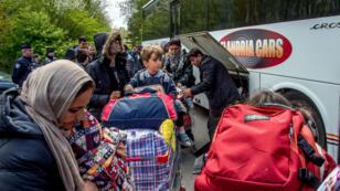 Des migrants montent dans un bus pour rejoindre un gymnase du département après l'incendie du camp, le 14 avril.