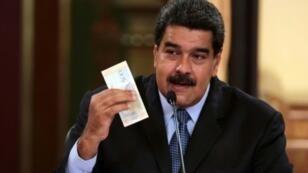 صورة موزعة نشرتها الرئاسة الفنزويلية تظهر الرئيس نيكولاس مادورو يستعرض عملة جديدة خلال بث تلفزويني من القصر الرئاسي في كراكاس بتاريخ 17 آب/أغسطس 2018