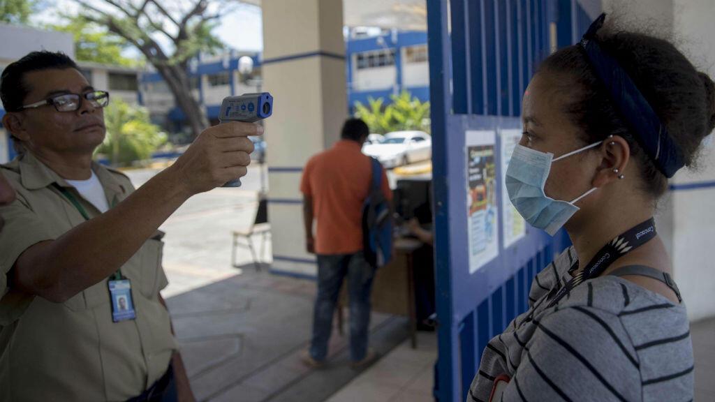 Un guardia de seguridad toma la temperatura a una mujer en la entrada de la Universidad Nacional de Ingeniería (UNI) en Managua, Nicaragua.
