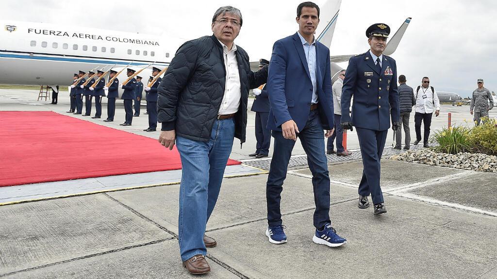 El líder de la oposición venezolana, Juan Guaido, llega a la base aérea de CATAM con el Ministro de Relaciones Exteriores de Colombia, Carlos Holmes Trujillo García, en Bogotá el 24 de febrero de 2019