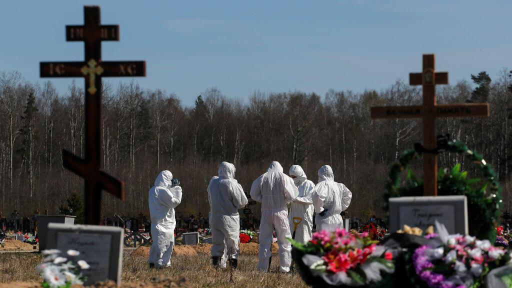 Los sepultureros que usan equipo de protección personal (EPP) se reúnen después de enterrar a una víctima del nuevo coronavirus Covid-19 en la sección de propósito especial de un cementerio en las afueras de San Petersburgo, Rusia, el 5 de mayo de 2020.