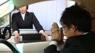 Prier devant une petite boîte avant de reprendre sa route, voilà un bien étrange service funéraire.