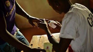 Un électeur trempe son doigt dans l'encre, à Bujumbura.