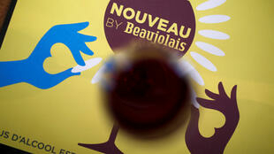 A glass of wine against a backdrop advertising Beaujolais Nouveau in a bistrot in Paris on November 21, 2019.