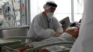 Una empleada de la salud atiende a un paciente en una unidad de cuidados intensivos para enfermos de Covid-19, en el Hospital El Tunal, en Bogotá, Colombia.