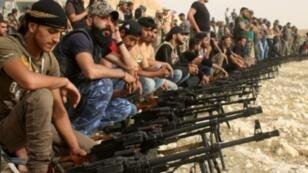 مقاتلون من المعارضة السورية خلال عرض لأسلحتهم قرب مدينة درعا في 7 حزيران/يونيو 2018