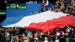 Los fanáticos de Francia se muestran en la bandera francesa durante el partido entre el francés Julien Benneteau y Nicolas Mahut y el español Marcel Granollers y Feliciano López en la  Semifinal del grupo mundial Francia v España, en el Stade Pierre Mauroy, en Lille, Francia, el 15 de septiembre de 2018.