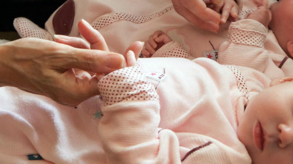 Un couple tient les mains de deux bébés nés d'une mère porteuse, en Ukraine, en avril 2011.