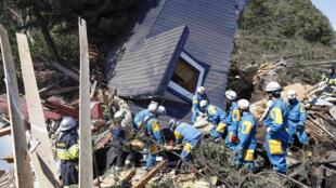 Los trabajadores de rescate buscan supervivientes de una casa dañada por un deslizamiento de tierra causado por un terremoto en la ciudad de Atsuma, Hokkaido, Japón, en esta foto tomada por Kyodo el 6 de septiembre de 2018.