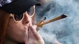 Une manifestante fume du cannabis devant le Parlement d'Ottawa, le 20avril 2018.