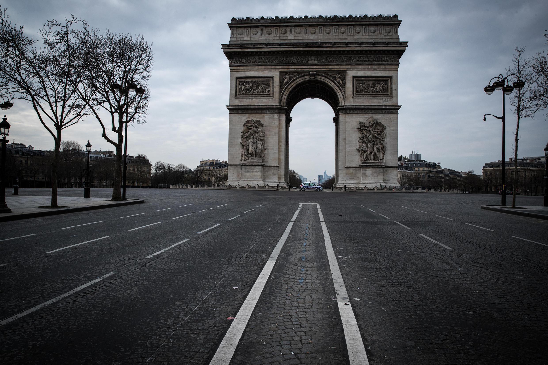 Le 17 mars 2020 à Paris, pas un passant, pas une voiture ne circule autour de l'Arc de Triomphe, axe de la capitale, habituellement bondé.