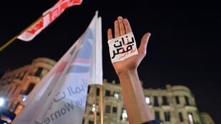 "An Egyptian protester holds up his hand with a slogan reading in Arabic: ""Egyptian girls are a red line"" during a 2013 demonstration in Cairo against sexual harassment"