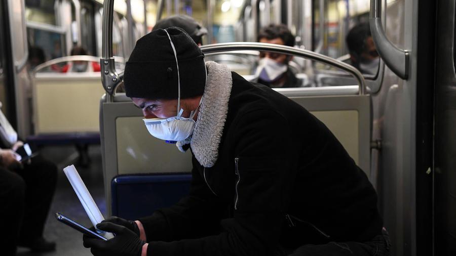 Un homme portant un masque de protection consulte son smartphone dans le métro, le 23 mars 2020 à Paris pendant l'épidémie de coronavirus