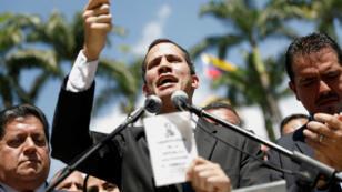 El presidente de la Asamblea Nacional Juan Guaidó sostiene una copia de la Constitución Nacional de Venezuela durante una rueda de prensa el 21 de enero de 2019 en Caracas.