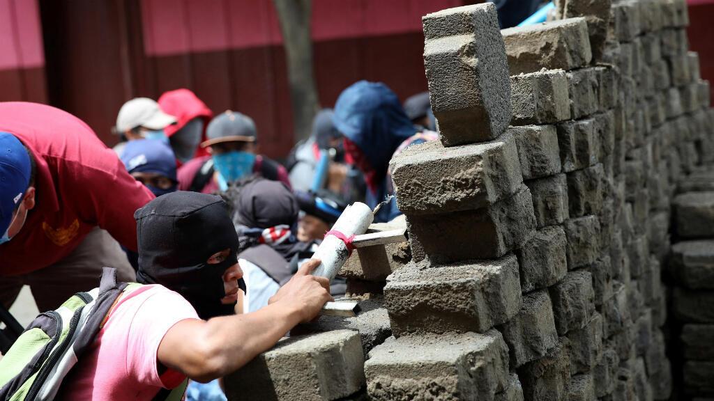 Los manifestantes se refugian en una barricada durante una protesta contra el gobierno del presidente nicaragüense Daniel Ortega en Masaya, Nicaragua. 19 de junio de 2018.