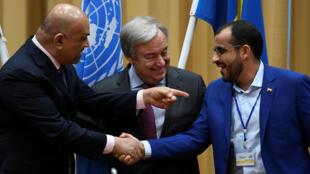 El jefe de la delegación hutí, Mohammed Abdul-Salam, y el ministro de Exteriores yemení, Khalid al-Yamani, se estrechan la mano junto al secretario general de la ONU, António Guterres, en el cierre de las conversaciones de paz para Yemen en Rimbo, Suecia, el 13 de diciembre de 2018.