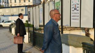 جزائري يتأمل ملصقات انتخابية في الجزائر العاصمة 2017