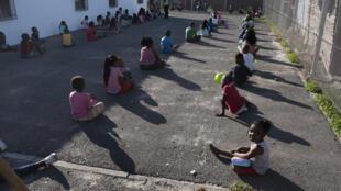 Los niños de una escuela infantil sudafricana aguardan en filas sentados en el suelo el 14 de mayo de 2020 en Langa, cerca de Ciudad del Cabo