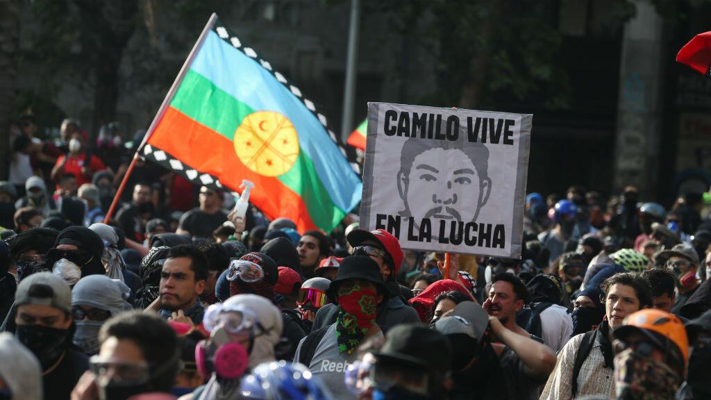 """Los manifestantes sostienen una bandera mapuche y una pancarta que dice """"Camilo vive en la lucha"""" mientras participan en una protesta contra el gobierno de Chile en Santiago, Chile, el 14 de noviembre de 2019."""