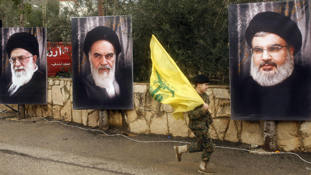 Un jeune garçon défile devant les portraits de Hassan Nasrallah, et des guides suprêmes iraniens.