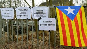 Carteles en los que simpatizantes de Carles Puigdemont piden su liberación junto a una bandera de Cataluña. 26 de marzo de 2018.