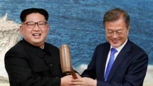 صورة التقطت بتاريخ 27 نيسان/أبريل 2018 تظهر زعيم كوريا الشمالية كيم جونغ أون (يسار) والرئيس الكوري الجنوبي مون جاي إن يقسمان قالب حلوى يرمز إلى بدء المصالحة خلال عشاء رسمي في مانمونجوم