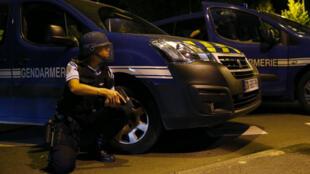 Un gendarme s'abrite derrière une voiture à Beaumont-sur-Oise samedi 23 juillet 2016.