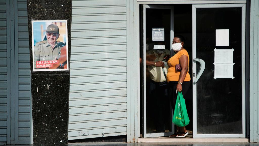 Esta mujer sale de una tienda en La Habana, Cuba, el 9 de mayo de 2020 durante la pandemia del Covid-19. A la salida del negocio, hay un afiche con la cara del expresidente Raúl Castro.
