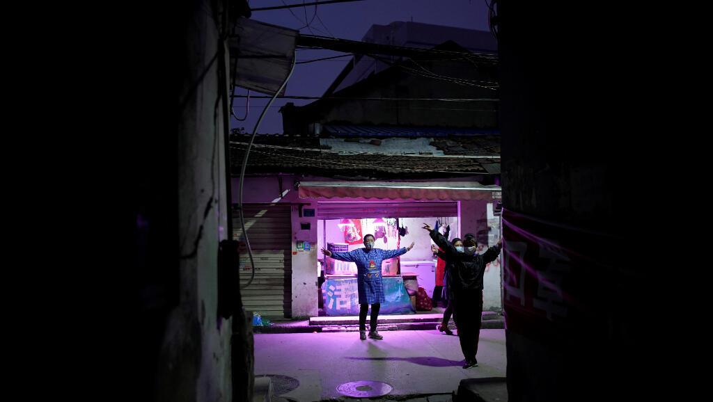 Los habitantes de un barrio en Wuhan, en la provincia china de Hubei, bailan en las calles con mascarillas para protegerse aún del Covid-19, el 5 de abril de 2020.