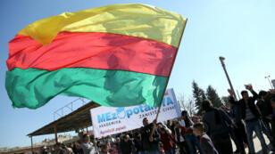 Un homme agite l'emblème du PYD lors d'une manifestation à Qamishli le 4 février 2016.