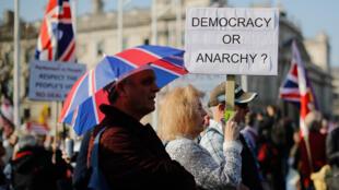 Una manifestante pro-Brexit sostiene un cartel mientras se reúne con otros afuera de la Cámara de los Comunes en el centro de Londres el 29 de marzo de 2019.