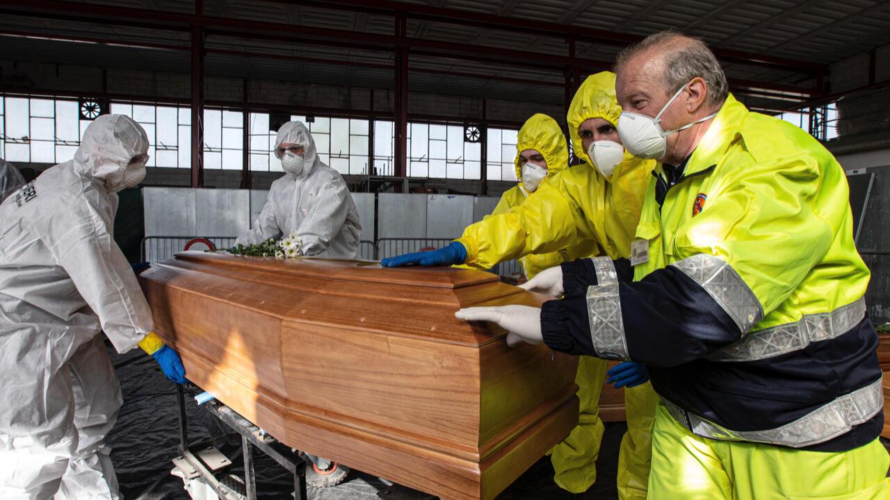 Archivo: Oficiales de carabineros italianos, junto a miembros del Ejército y Protección Civil, cargan los ataúdes de personas fallecidas a causa del coronavirus en autos funerarios militares, en Ponte San Pietro, norte de Italia, el 28 de marzo de 2020.