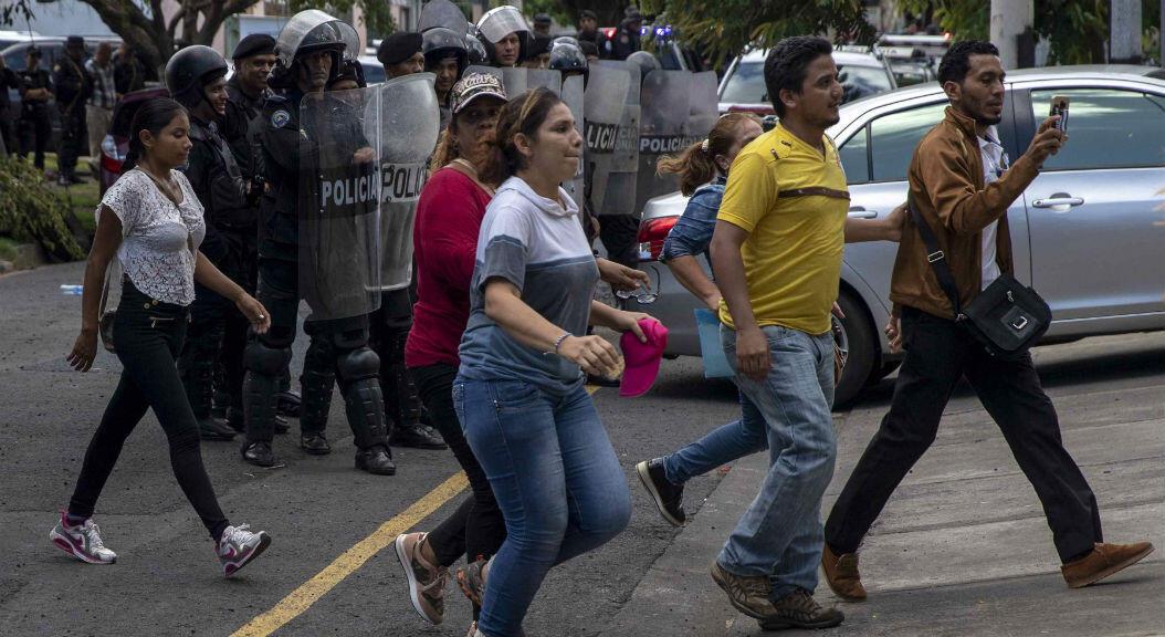 Miembros antidisturbios de la policía nacional realizan un cordón de seguridad frente a varios manifestantes, tras una conferencia de prensa en demanda para liberar a más de 80 manifestantes encarcelados,en Managua, Nicaragua, el 19 d ejunio de 2019.