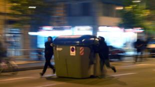 متظاهرون يدفعون حاوية قمامة خلال مواجهات مع الشرطة في برشلونة ليل 19 شباط/فبراير 2021