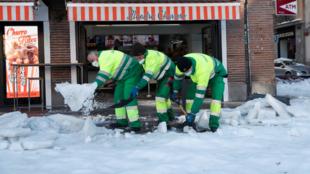 Trabajadores municipales retiran nieve en la entrada de un comercio de Madrid, España, el lunes 11 de enero de 2020.