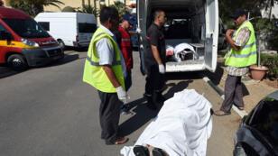 Des ambulanciers tunisiens se préparent à transporter le corps d'une des victimes de l'attentat de Sousse, le 26 juin 2015.