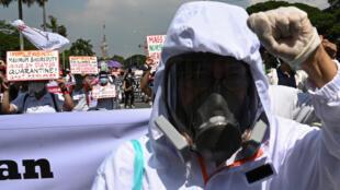 عامل في المجال الصحي يضع قناعاً واقياً خلال مسيرة في مانيلا في الفيليبين في 27 تموز/يوليو 2020 قبيل خطاب الرئيس رودريغو دوتيرتي إلى الأمة