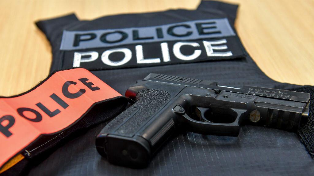 Un pistolet, un dossard et un brassard de policier.