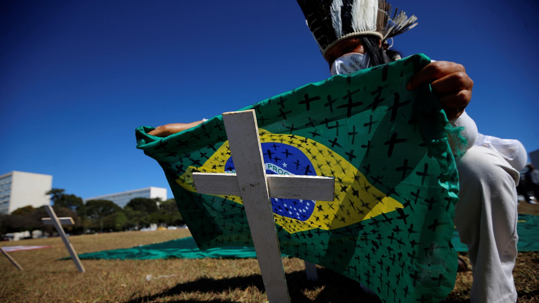 Un activista coloca una bandera brasileña pintada con cruces en una cruz que simboliza a los que murieron por el coronavirus frente al Congreso Nacional durante una protesta contra el presidente de Brasil, Jair Bolsonaro, en Brasilia, el 14 de julio de 2020.