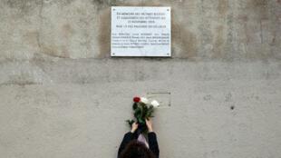 Une femme dépose une gerbe de fleurs sur une plaque commémorative installée près des restaurants du Carillon et du Petit Cambodge, à Paris, le 13novembre2018.