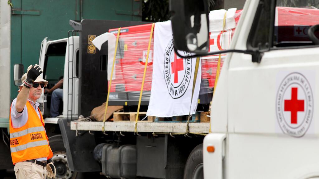 Un trabajador dirige los camiones con el logotipo de la Federación Internacional de Sociedades de la Cruz Roja y de la Media Luna Roja (FICR) que transportan ayuda humanitaria.